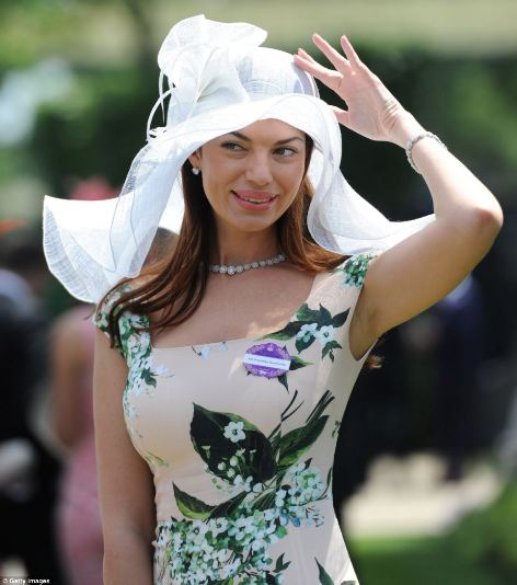 a lady in a beige and forest green floral dress and chic white floppy fascinator hat on day 5 of Royal Ascot 2014