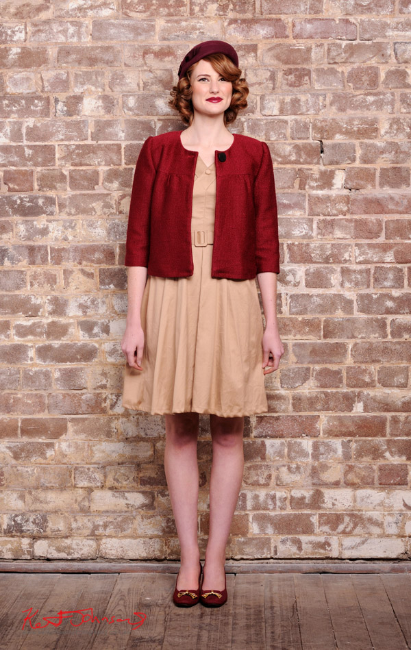 Vintage Fashion - beige cotton dress with red jacket and Beret photographed against a distressed brick wall in the studio - studio fashion photography