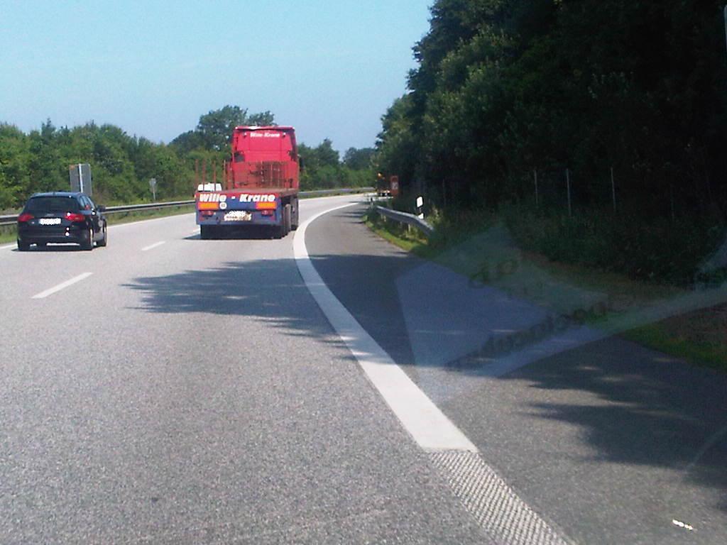 LKW mit schief hängendem Anhänger, Autobahn, grüne Büsche, blauer Himmel, roter LKW