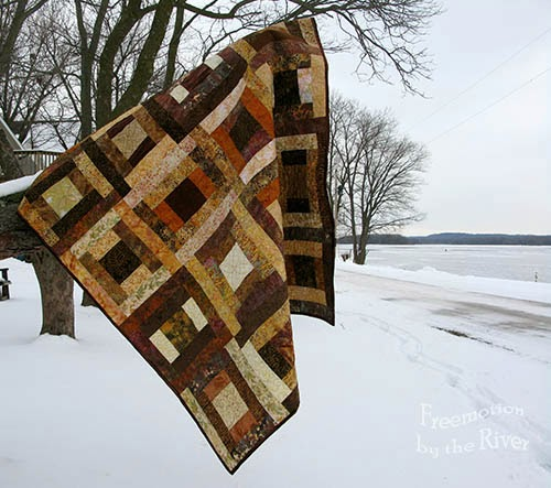 Brown batik quilt hanging in a tree at Freemotion by the River