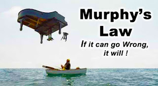"Photo composition of small boat floating over the ocean with a piano and stool falling off the sky. There is the legend: ""Murphy's Law"" ""If it can go Wrong, it will !"""