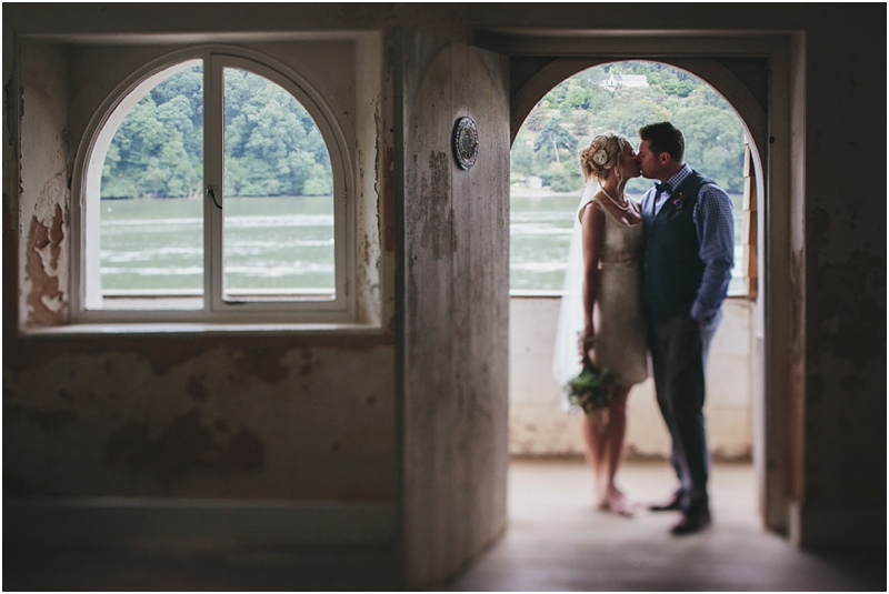 Bride and groom kissing in the Boathouse at Greenway House