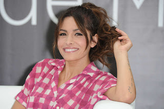 Sarah Shahi twirling her hair at a Monaco photocall