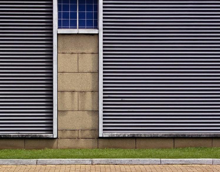 Junto ao passeio, parede forrada a chapa ondulada, dando linhas na horizontal. Sobre a esquerda, intervalo ao alto, em pedra com janela em cima.