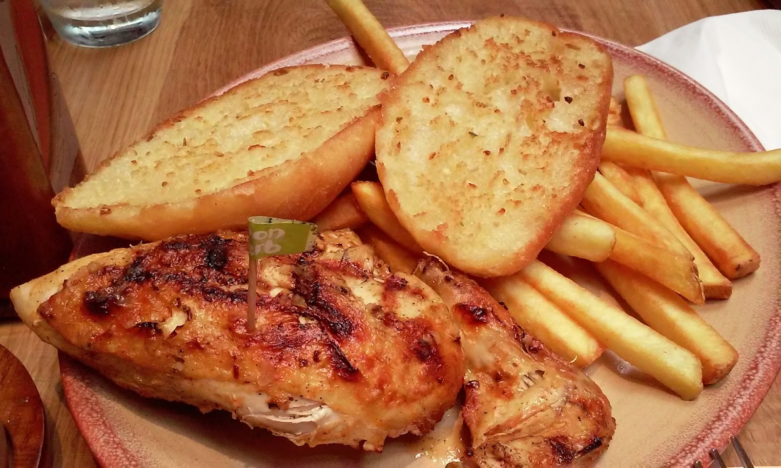 Grilled chicken with herb, garlic bread and fries.