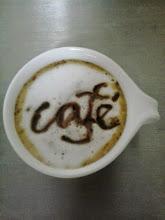 Un café escrito por Mónica con salsa de chocolate sobre la espuma.