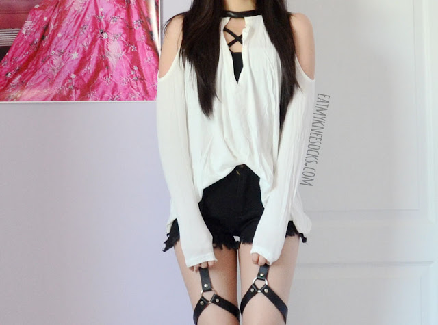 An edgy, grunge-style outfit with the leather-trim cold shoulder SheIn top, a strappy bralette, Harajuku-style black harness shorts, and spiked high-heel booties.