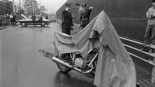 December 10, 1968 police officers inspecting a motorcycle used in the 300 million yen robbery