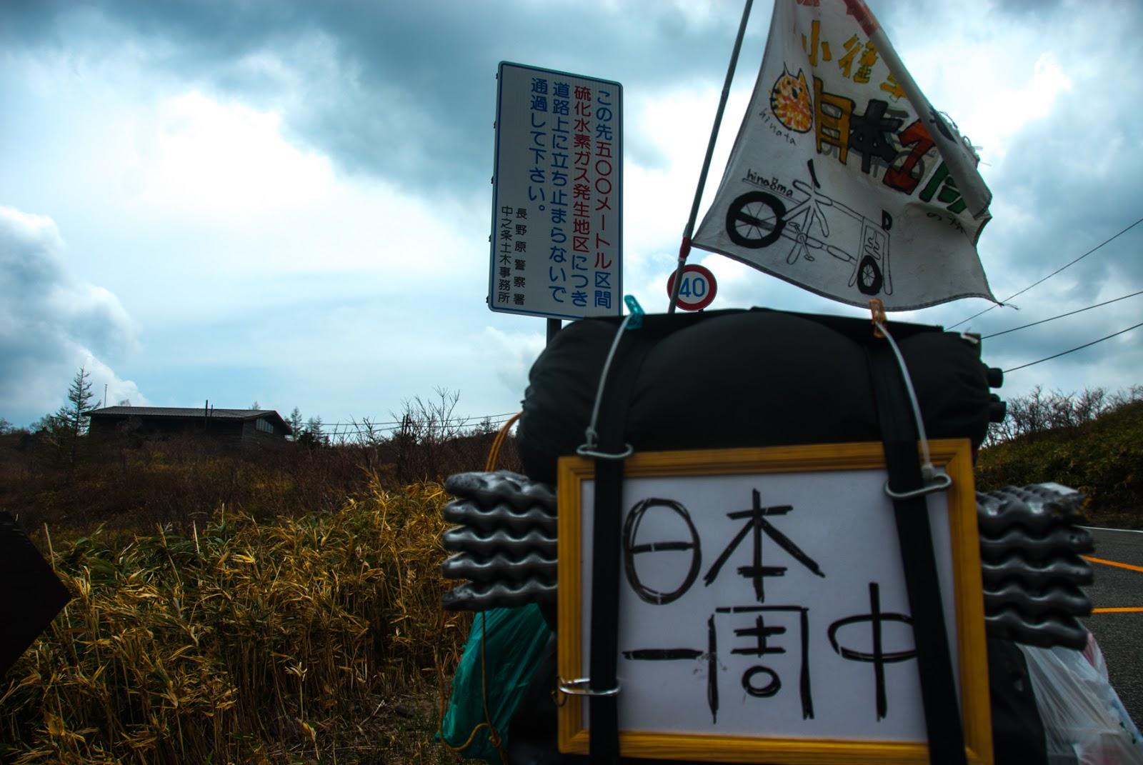 毒ガス地点手前で日本一周中の看板と旗を掲げた自転車