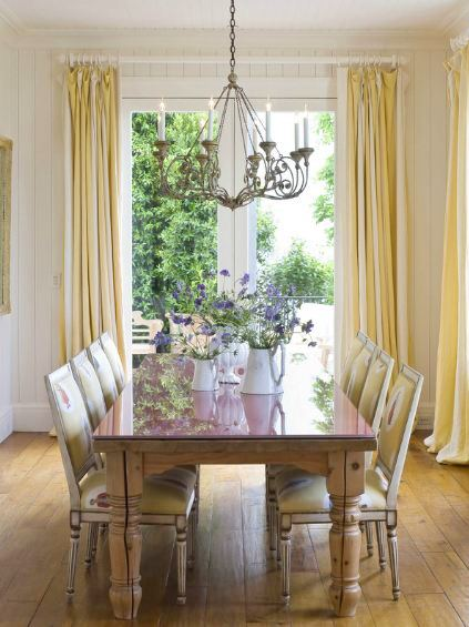 dining room in a san francisco mansion with rustic white wood table and matching upholstered chairs with nail head trim, white paneled walls, yellow floor length curtains, an iron work chandelier and a large glass door opening to a green backyard