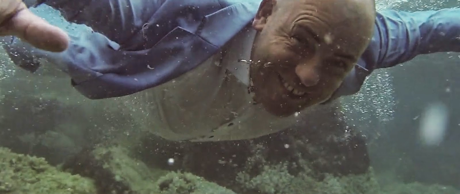 A man in a light blue slcks, suit jacket and open neck off white shirt swimming underwater fully clothed.