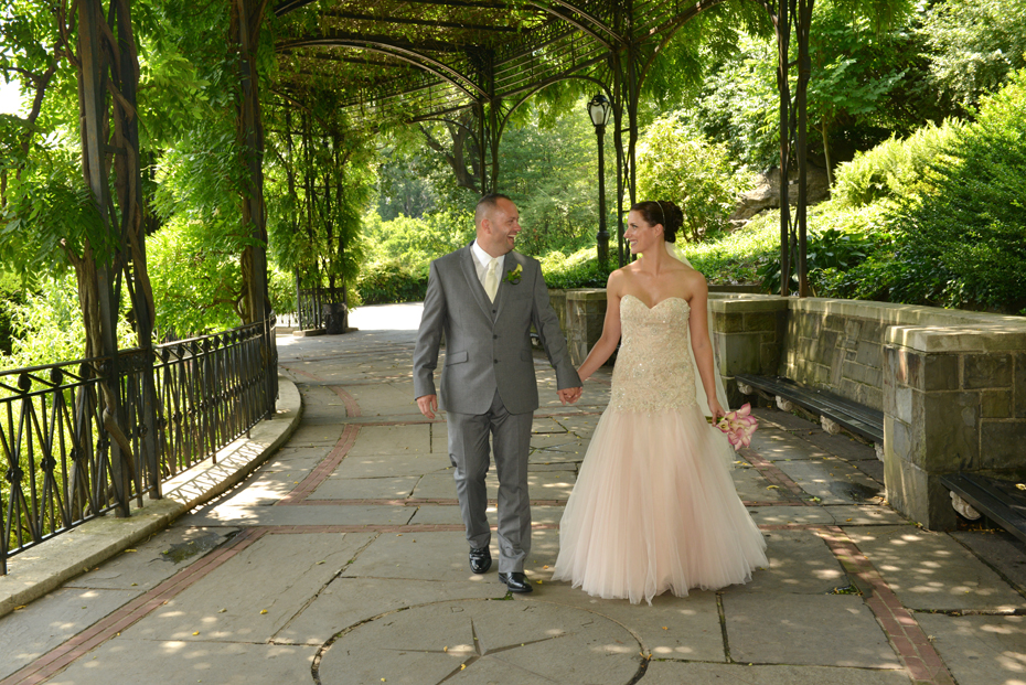 Newlyweds Walking through Wisteria Pergola