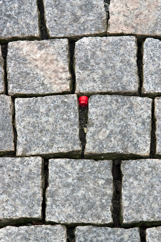 red cap in sidewalk