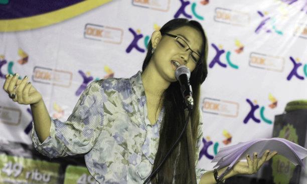 Seorang wanita sedang membaca puisi. Gambar: dokdenpasar.com
