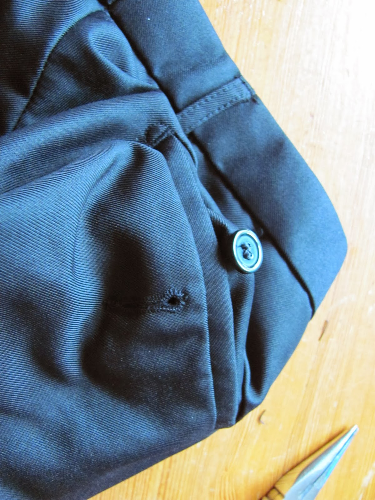 Repairing the back pocket button on black slacks