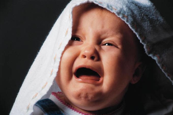 صورة طفل رضيع يبكي وهو يغطي رأسه بمنشفة