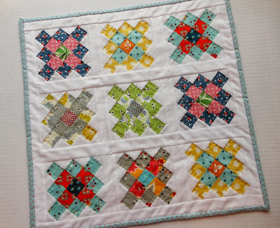 a doll quilt made with denyse schmidt fabrics using a granny square pattern