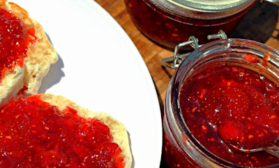strawberry raspberry jelly on an english muffin with a jar of jelly next to it