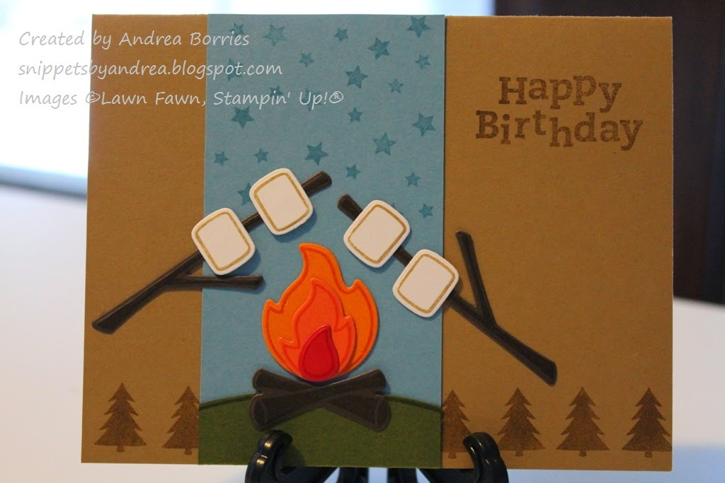 Tan birthday card with a vertical blue piece. On the blue is a green hill with a campfire. Two sticks with marshmallows are over the fire, and stars are stamped at the top of the blue piece.