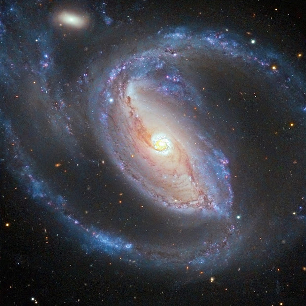 NGC 1097 and NGC 1097A spied in a galactic embrace!