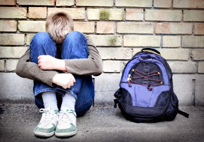 Sad Teen Boy Is Seated with a Backpack - Source: http://www.stopbullying.gov/blog/2013/12/30/bullying-and-suicide-whats-the-connection