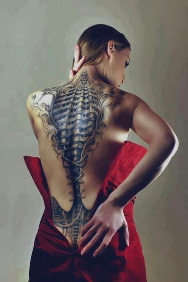 Chica con tatuaje 3d en la espalda que parece un corse de piel y debajo se ven las costillas que son de metal