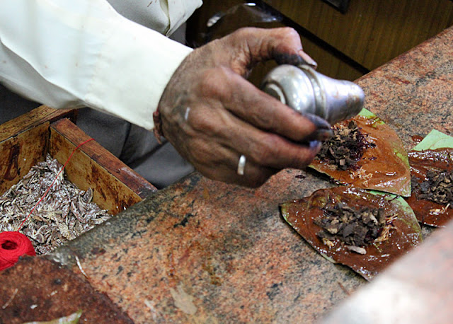 paan maker adding spices to a betel nut leaf