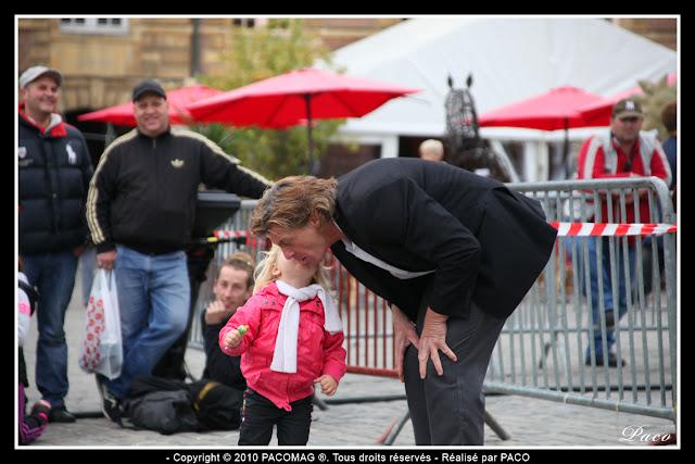 Une petite fille embrasse Philipe, artiste de rue, avant sa prestation Place Ducale Charleville Mézières festival des marionnettes.