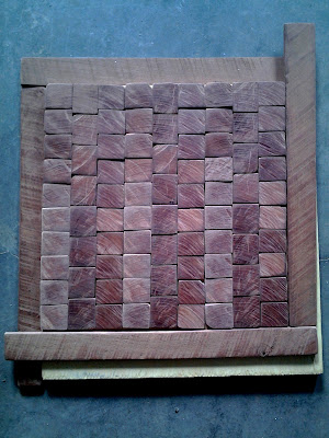 small end-grain tiles and rough-sawn slats cross cut from an aged hardwood timber, possibly Black Walnut