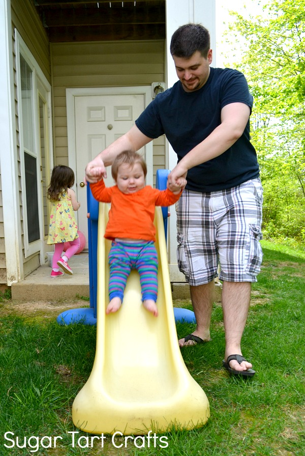 Dad helping toddler boy go down a slide