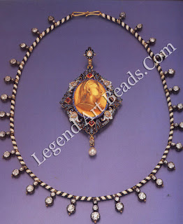 A gold fringe necklace by CARLO and ARTHUR GIULIANO, decorated with black and white enamel and set with Indian diamonds taken at the battle of Seringapatam in 1799. Within, a gold pendant by CARLO GIULIANO decorated with enamel and set with pearls and rubies. The central oval aperture contains a repou.sse gold portrait of Queen Victoria, who gave the jewel to her goddaughter, Alexandra Elizabeth Grey.
