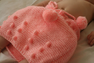 Neve wearing pink knitted pom-pom skirt.