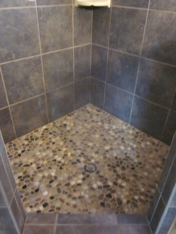 porcelain corner shower with pebble stone floor title=
