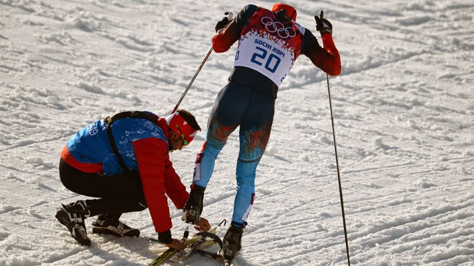 Canadian coach skier crouched down to help a Russian skiier with his skis.