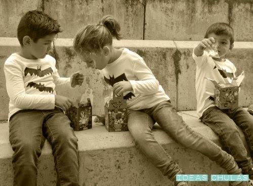 3 niños con la camiseta de Halloween y cajitas con dulces
