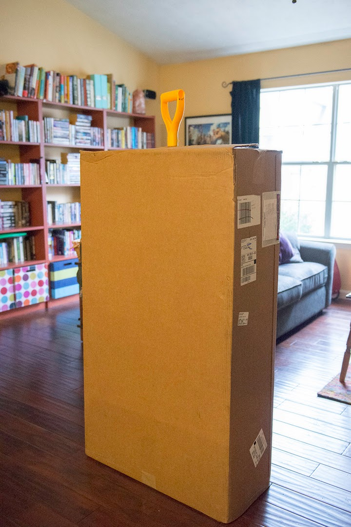 Photo of a huge box with a shovel top sticking out of it.