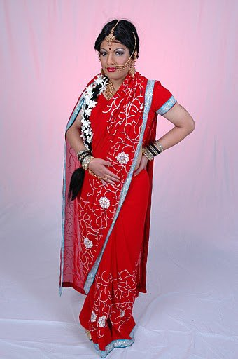 in Red Saree with long wavy hair and jasmine on her hair is a man