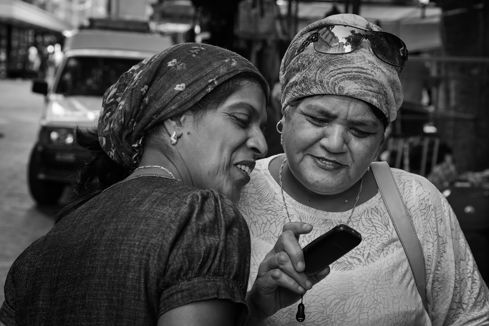 Two women looking at a cell phone in this South African street photograph