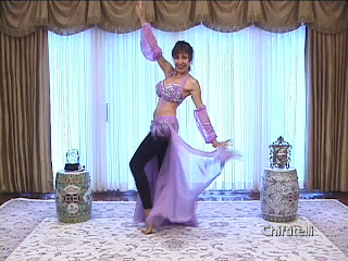 Shamira in pink costume practicing bellydance moves
