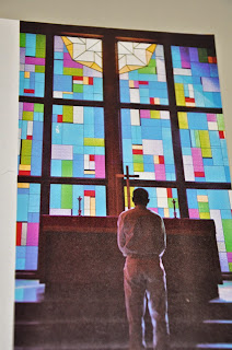 An inmate stands before a stained glass window in the TDCJ chapel.