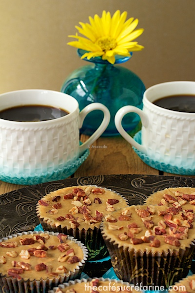 A photo of a serving plate of Brown Sugar Biscoff Sheet Cake Cupcakes with two cups of coffee and a flower vase in the background.