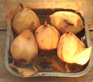 Pears roasted in perry with whisky cream. Five poached pears in a dish.