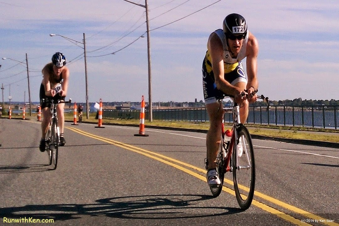 Up-close action photo of two cyclists, bicycling on their aero bikes at the Whaling City Triathlon in New Bedford, MA.  Sports Photography from Inside the Pack by Ken Skier.