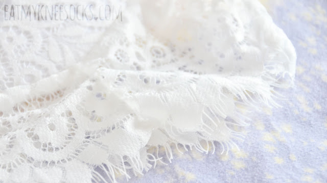 Details on Dresslink's white lace bralette, a dupe of the For Love and Lemons She's a Knockout Bra, with scalloped lace edges, padded cups, delicate embroidery, adjustable straps, and a hidden zipper.