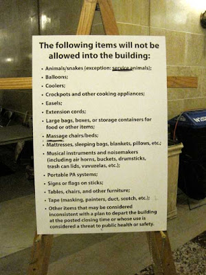 Large sign on an easel with long list of prohibited items