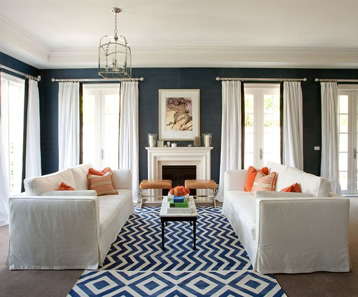Living room with blue walls, dueling white sofas with orange accent pillows, and a blue and white geometric rug