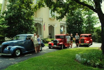 three red street rod cars parked in front of the main house here for the street rod nationals with the guests standing next to their cars