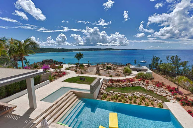 Ocean, swimming pool and the backyard as seen from the modern villa