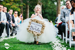 "The flower girl at David and Laura's wedding carrying a ""Here Comes the Bride"" sign"