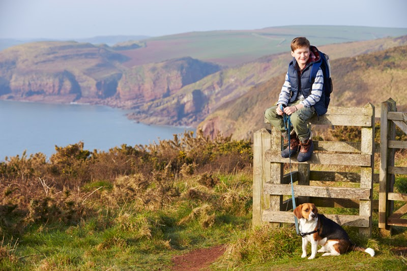 A boy and his dog on a coastal path in England